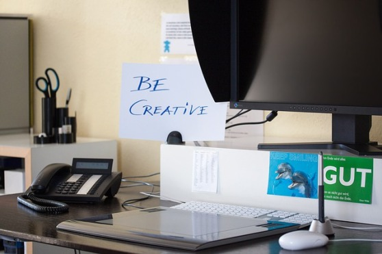 "A close-up of a desk with a computer, corded phone, and office supplies. Behind the desk is a sign that reads, ""Be creative""."