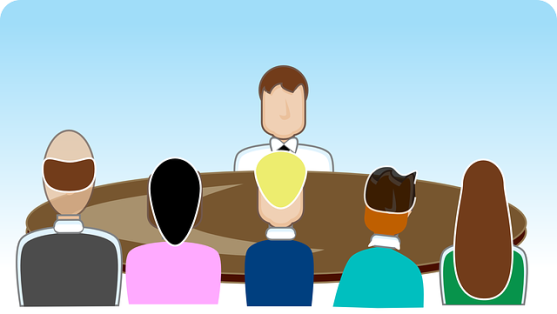 A cartoon of a manager sitting on one side of a table across from five employees.