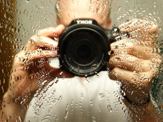 A photographer holds a camera up to a mirror. Drops of water dot the mirror as if orbiting the lens.