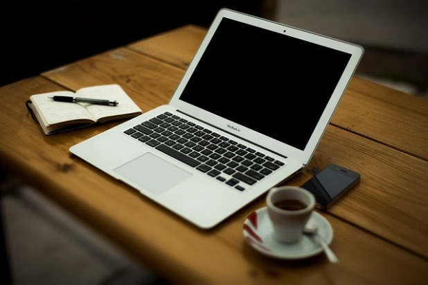 A wooden desk on which sits a Macbook Air laptop, a cup of coffee with saucer and spoon, a smartphone, and a notebook and pen.