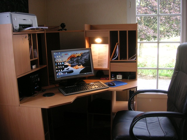 a home office with a high backed office chair and wooden desk with fairly neat