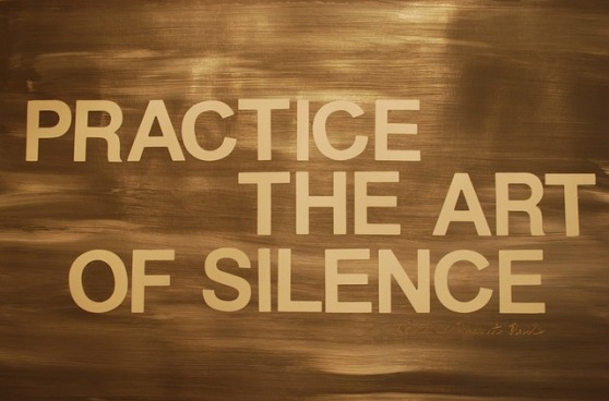 "A golden brown background with golden text that reads ""Practice The Art of Silence"""