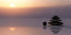 A calming image of a sunset, reflective water, and a pile of stones.
