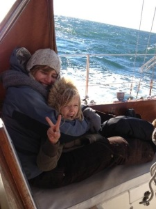 Melanie Zurek and her daughter hug while sailing on a boat.