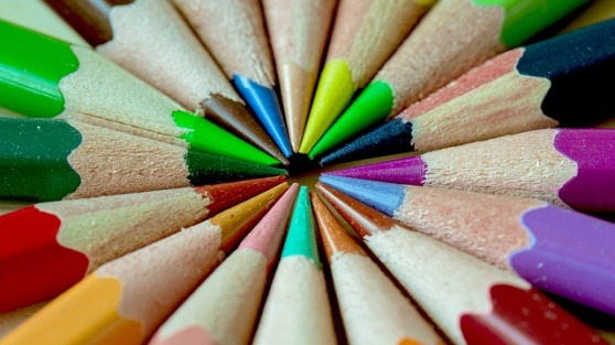 Various color pencils are arranged so that there tips meets to create a small inner circle.